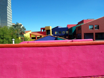 Many colorful buildings with a pink wall in the foreground.